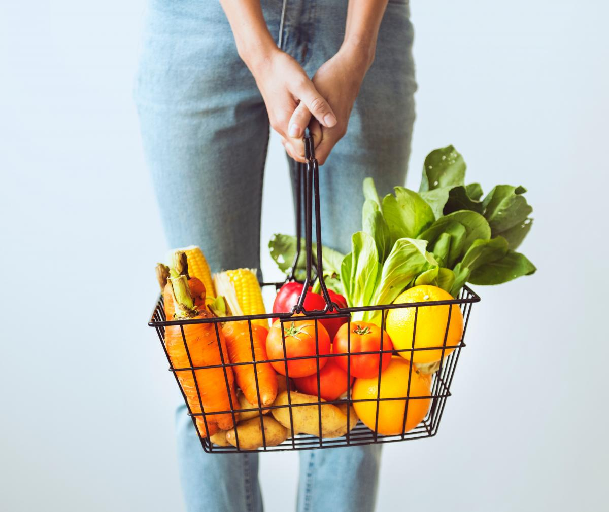 Photo of a person holding a basket full of groceries