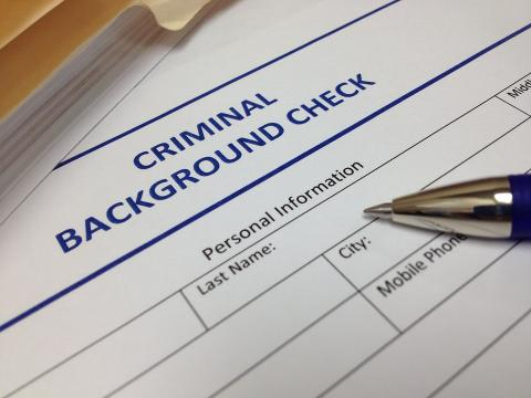 A pen sits on a criminal background check form