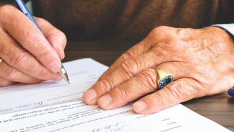 A senior signs documents with a pen
